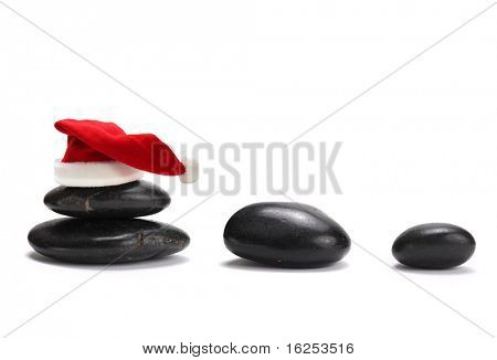 stack of stones with red santa claus hat