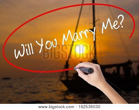 Woman Hand Writing Will You Marry Me? With A Marker Over Transparent Board
