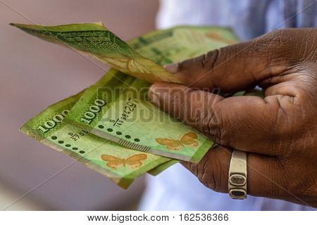 Closeup photograph of hands counting srilankan rupies