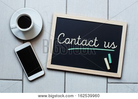 Chalkboard or Blackboard concept saying - Contact Us - with coffee and mobile phone.