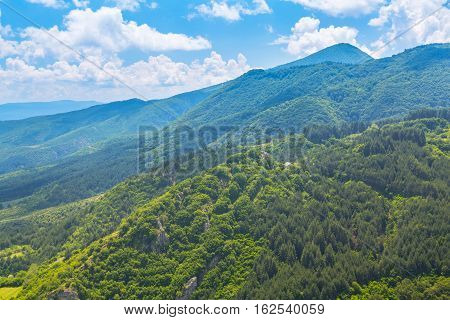 Rhodope mountains summer panorama with green pine trees and blue cloudy sky