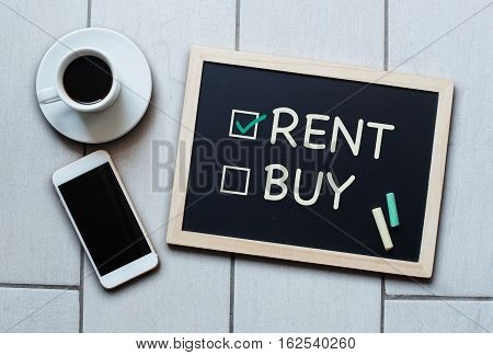 Rent not Buy blackboard concept. Choosing renting over buying with coffee and mobile phone