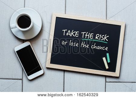 Chalkboard or Blackboard concept saying - Take the risk or lose the chance - with coffee and mobile phone. Business Personal Education Effective Management concept.