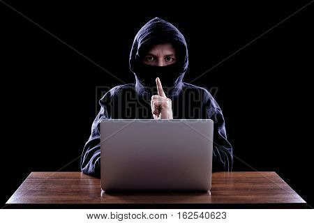 Hooded computer hacker stealing information with laptop. Dark background