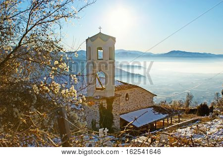 The old orthodox church with a cemetery surrounded by winter garden with the foggy valley of Kastoria on the background Greece.