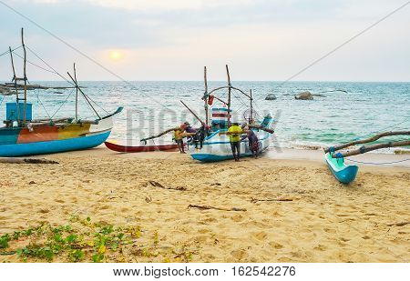 The crew of the catamaran-boat steers it to the sandy shore at the sunset after the fishing Hikkaduwa Sri Lanka.