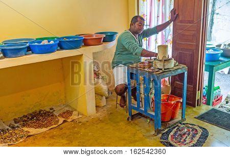 MEETIYAGODA SRI LANKA - DECEMBER 5 2016: The jeweler at his workplace cuts the gems on December 5 in Meetiyagoda.