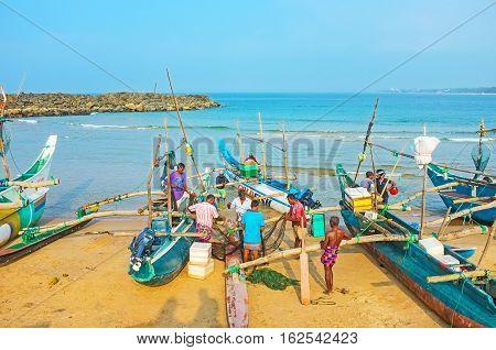HIKKADUWA SRI LANKA - DECEMBER 5 2016: The fishermen unwind and fold the net to their boat at the fishing harbor on December 5 in Hikkaduwa.