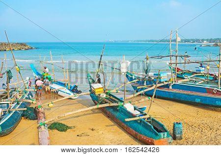 HIKKADUWA SRI LANKA - DECEMBER 5 2016: The old catamaran-boats on the sandy shore of the harbor on December 5 in Hikkaduwa.