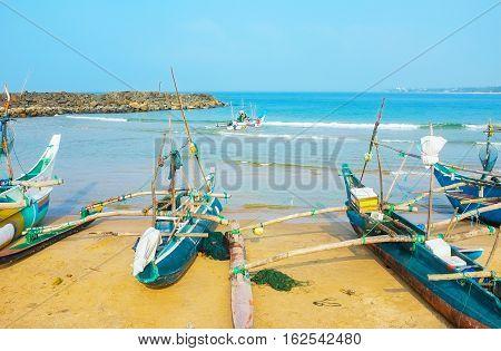 HIKKADUWA SRI LANKA - DECEMBER 5 2016: The fishing port is full of traditional catamaran-boats on December 5 in Hikkaduwa.