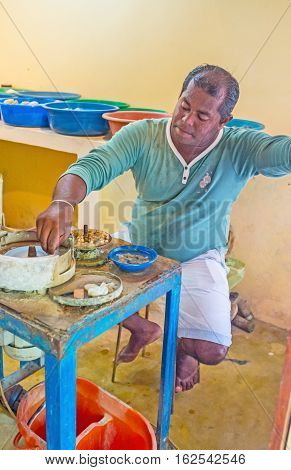 MEETIYAGODA SRI LANKA - DECEMBER 5 2016: The jeweler cuts the moonstone with the dimond blade in jewelry manufacture on December 5 in Meetiyagoda.