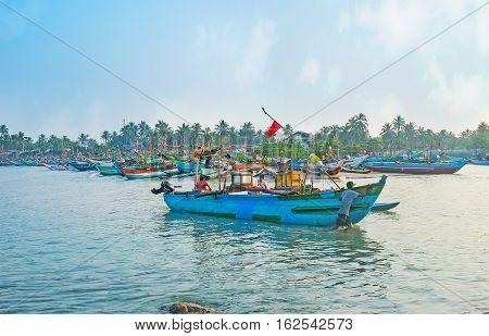 HIKKADUWA SRI LANKA - DECEMBER 5 2016: The fishermen back to the harbor and steer the colorful wooden catamaran boat to shore on December 5 in Hikkaduwa.
