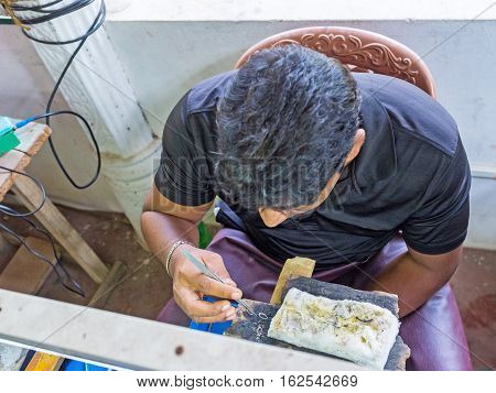 MEETIYAGODA SRI LANKA - DECEMBER 5 2016: The silversmith connects the silver details into the jewelry base on December 5 in Meetiyagoda.