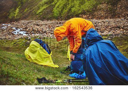 couple joyfull hikers on the trail in the Islandic mountains. Trek in National Park Landmannalaugar, Iceland
