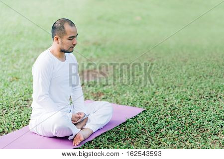 Handsome Asian man meditating on green grass in the park calm and focused health and yoga meditation concept with copy space