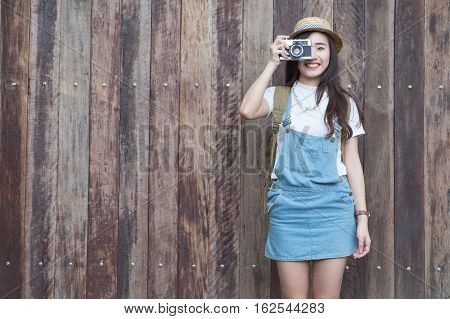 Young asian butiful woman with camera. in a blue shirt. Hipster fashion photographer girl. Young people vintage tone.