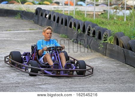 Boy Is Driving A Kart On Circuit