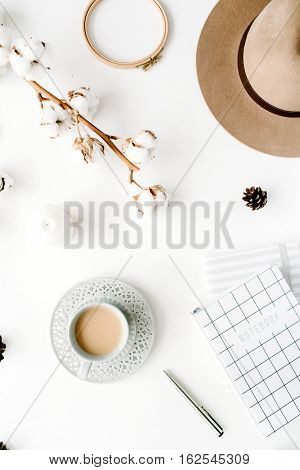 Flat lay trendy creative feminine accessories arrangement with coffee cotton branch and diary. Hat cotton branch notebook coffee cup fir cone on white background. Top view