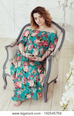 Young, extravagant, extraordinary pregnant girl, woman sitting on a chair in the flowerpot snake modern dress on a white background with a blue wall picture, embracing the belly.