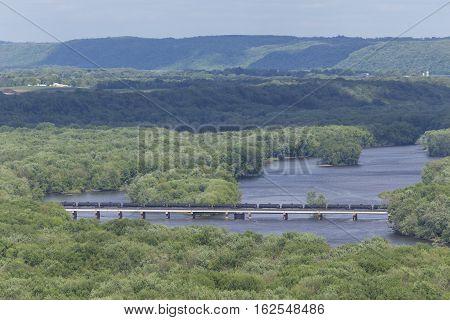 A train of tank cars crossing a bridge.