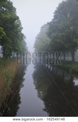 Mist covering the city channel in Breda giving mysterious white and grey landscape