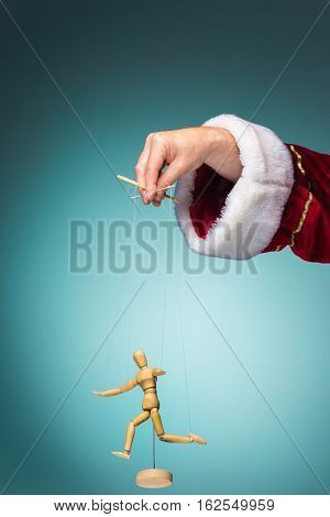 Image puppet in the hands of the Santa as puppeteer on blue background
