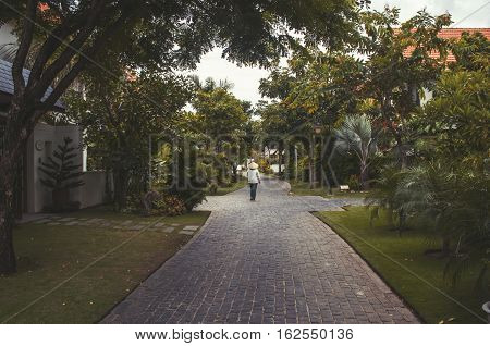 cozy street surrounded by greenery and lonely man in Vietnamese hat