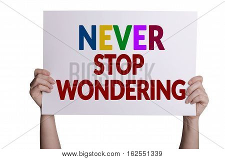 Never stop wondering card in hand isolated on white background