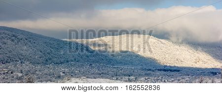 panoramic winter landscape a village in the foothills of snowy hills and the first rays of the rising sun in the early morning