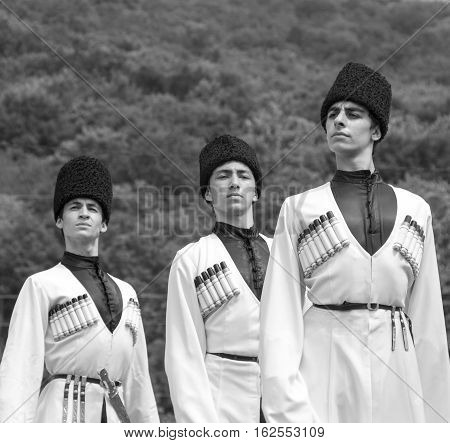 Adygea RUSSIA - JULY 25 2015: Young guys in Adyghe national costumes dancing traditional dance at an ethnofestival in the Foothills of Caucasus in Adygea
