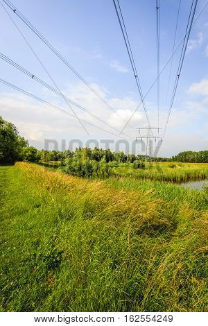 High voltage lines and pylons in a large nature reserve with small creeks in the Netherlands. It's a sunny day in the summer season.