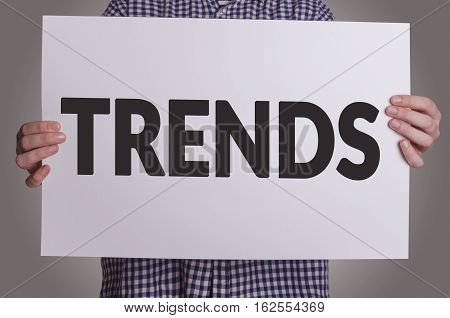 Businessman shows Trends card. Trend awareness improvement concept.