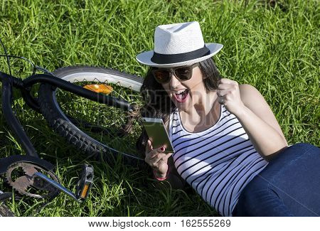 Young excited woman using device while lying on grass nearby bike. Lanzarote Gran Canaria Spain.