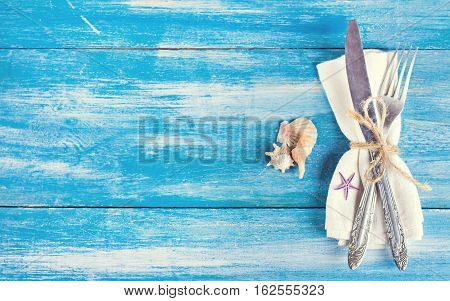 Table setting with a seaside theme. fork and knife napkin shells. Summer table setting in a nautical theme with space for text top view. table setting in maritime style. Marine theme. napkin cutlery and seashells on a blue background