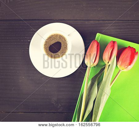 Coffee cup with note book and tulips