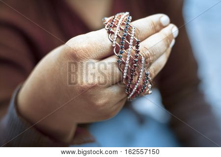 Girl wearing red top holding golden Bangle.