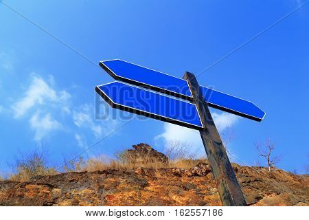 An image of blue empty guidepost with nature background.