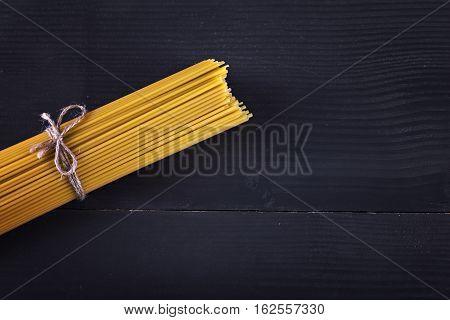 Yellow long spaghetti on black background. Thin pasta arranged in rows. Yellow italian pasta. Long spaghetti. Raw spaghetti bolognese. Raw spaghetti wallpaper. Thin spaghetti. Food background concept.