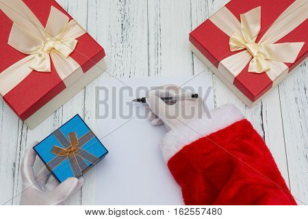 Santa Claus writing on a blank paper good for letter or advertisement and a gift box on the other hand