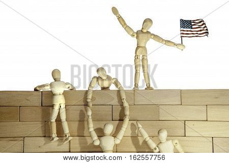 Model of anonymous people climbing a wall. One of the people holds the USA flag. Connotations are of illegal immigration at a border wall but also aspects of teamwork and success.