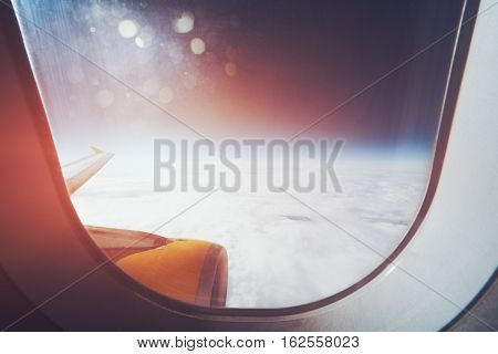 Beautiful wide view from window of aircraft: cloudscape horizon airplane wing and engine flare and stylish lens aura