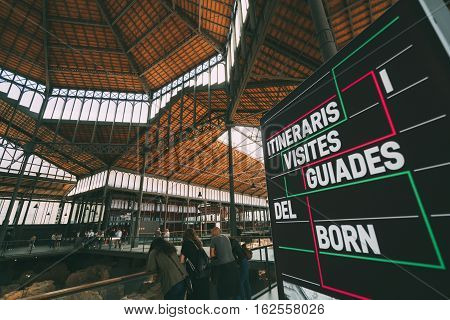 BARCELONA SPAIN - JUNE 2 2016. Wide view from inside of cultural center El Born. Old City Market museum with people watching exhibition and billboard with description in Spanish