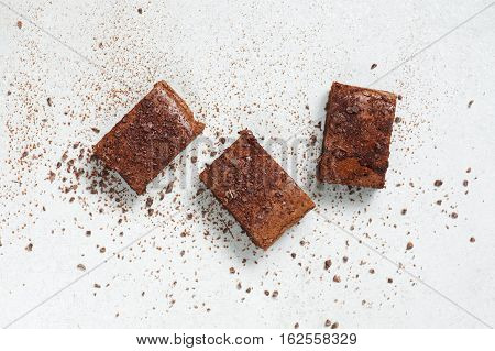 Three Pieces Of Brownie Topped With Chocolate Chips And Cocoa