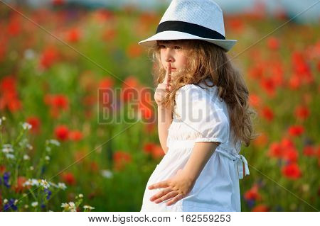 Portrait of kid girl making a hush gesture with finger on lips