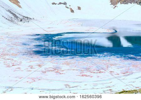 Floating melting ice blocks at the mountain lake in spring