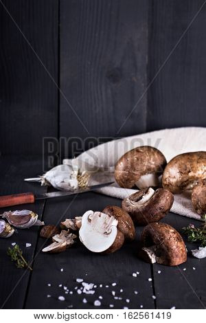 Fresh mushrooms with spices and herbs on a black board.Champignon mushrooms