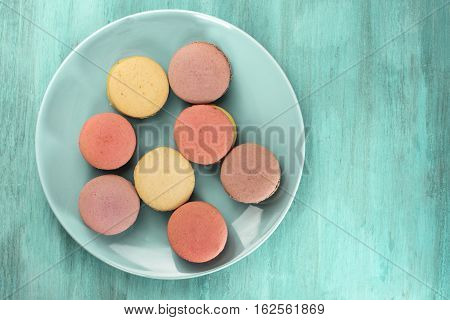 A photo of macarons on a teal blue plate, shot from above on a wooden background texture, with copyspace