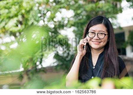 Portrait Of A Smiling Beautiful Asian Woman Talking With Her Phone