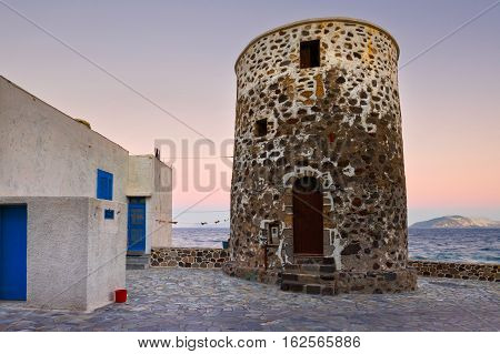 Windmill in Mandraki village and island of Giali in the distance.