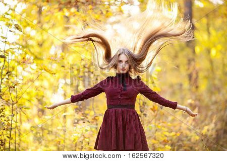 Beautiful young girl with long hair flying in the autumn forest standing in burgundy dress